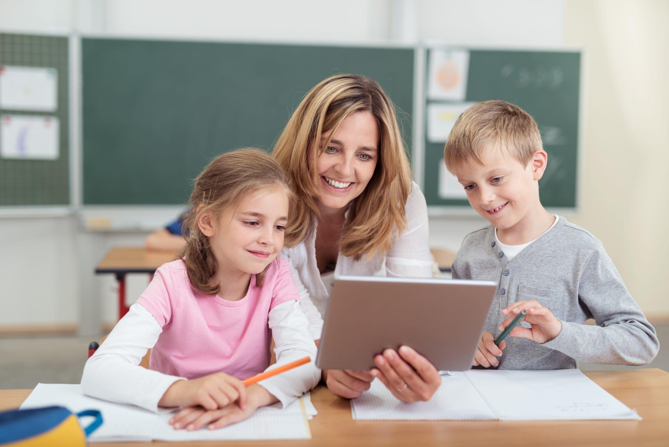 lehrerin zeigt kindern etwas am tablet